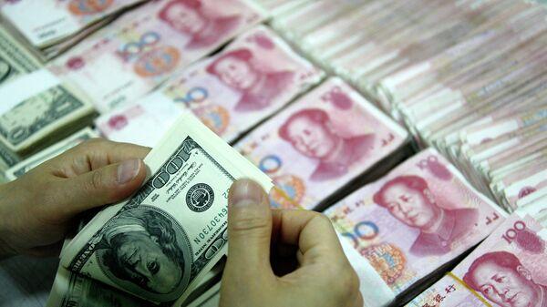 Доллары рядом с пачками юаней. Архивное фото