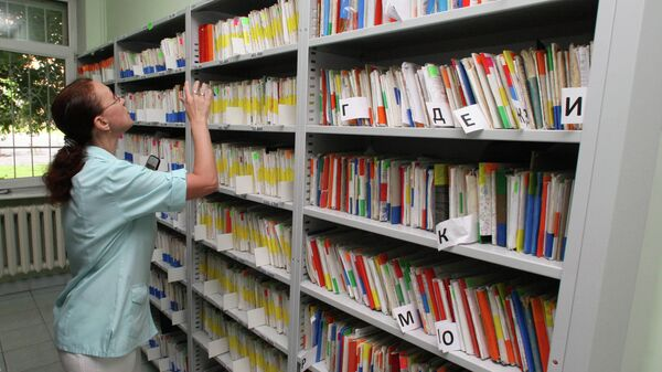 Сотрудник регистратуры работает с медицинскими картами пациентов в картотеке поликлиники. Архивное фото