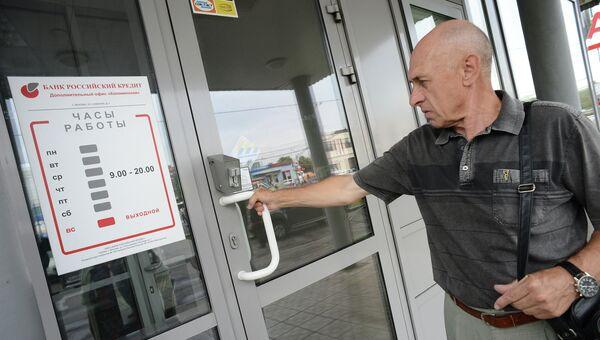 Мужчина у одного из офисов банка Российский кредит