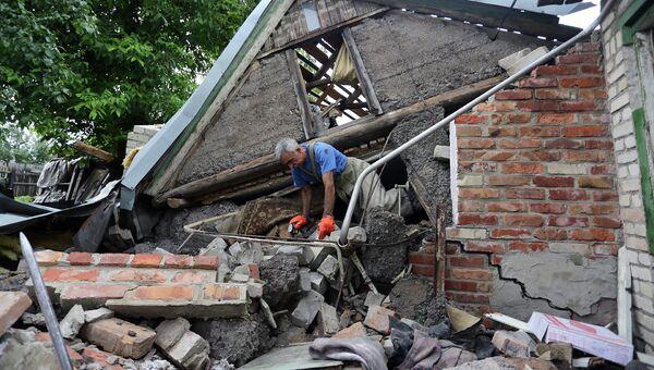 Спасатель возле разрушенного в результате обстрела дома в поселке Гольмовский Донецкой области. Архивное фото