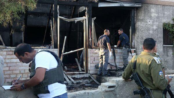 Сотрудники израильских сил безопасности у сгоревшего дома на западном берегу реки Иордан