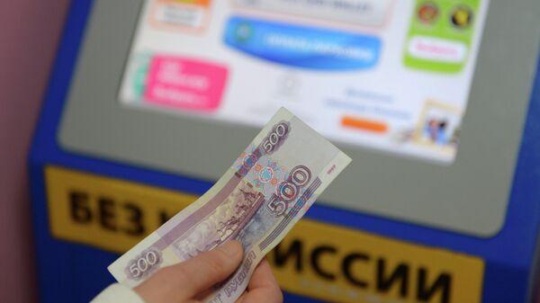 Жительница Москвы производит оплату услуг в одном из платежных терминалов QIWI
