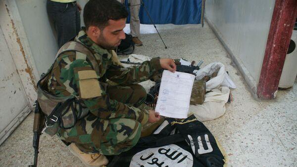 Сирийские военные досматривают оружие и вещи боевиков «Исламского государства». Архивное фото