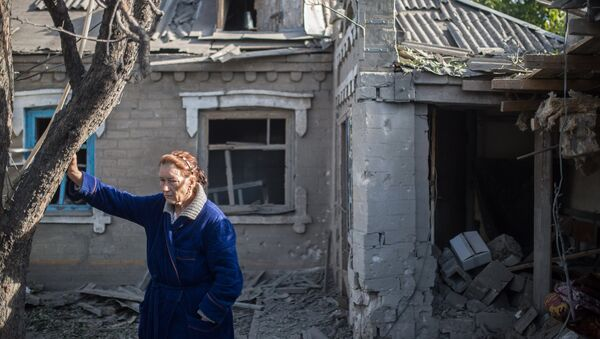 Женщина у поврежденного в результате обстрела дома в поселке Александровка. Август 2015