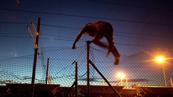 Мигрант пытается пробраться в Евротоннель в Кале, Франция. Архивное фото