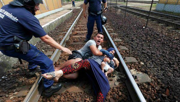 Венгерские полицейские задерживают семью мигрантов