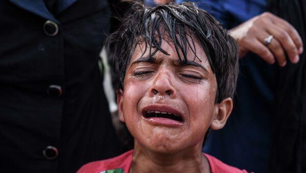 Ребенок плачет после применения венгерской полицией слезоточивого газа во время столкновений с мигрантами на границе Венгрии и Сербии. 16 сентября 2015