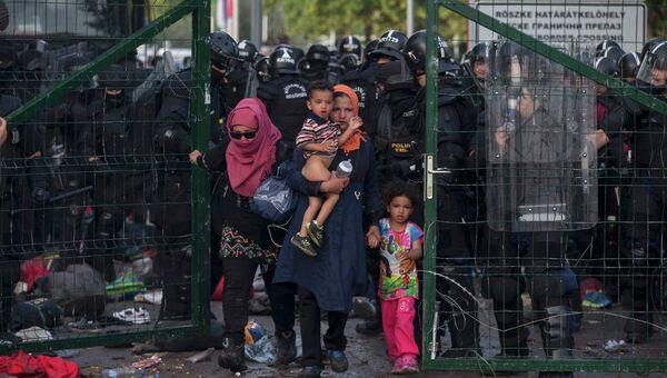 Венгерские полицейские отправляют мигрантов на территорию Сербии после столкновений на границе. 16 сентября 2015