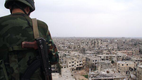 Военнослужащий сирийской армии на крыше одного из зданий, разрушенных в результате боевых действий, в Хомсе. Архивное фото