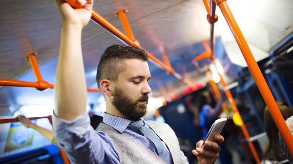 Пассажир в автобусе пользуется смартфоном. архивное фото