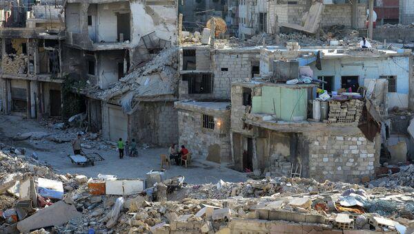 Местные жители на улице среди разрушенных зданий в районе Дахания в Дамаске. Архивное фото