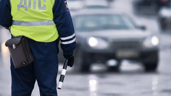 Сотрудник ГИБДД регулирует движение на Ленинградской площади в Омске
