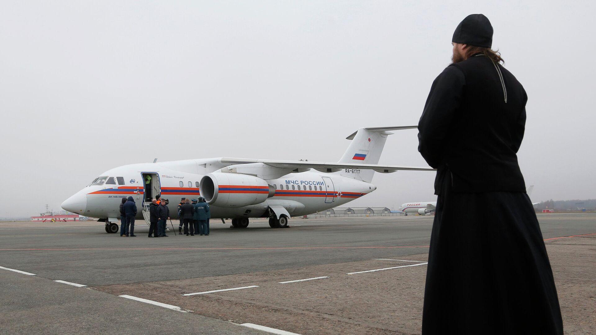 Священнослужитель наблюдает в аэропорту Пулково в Санкт-Петербурге за самолетом МЧС России, доставившим тела жертв крушения Airbus A321 авиакомпании Когалымавиа - РИА Новости, 1920, 16.09.2021