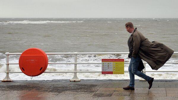 Мужчина на набережной. Уэльс, Великобритания. Ноябрь 2015