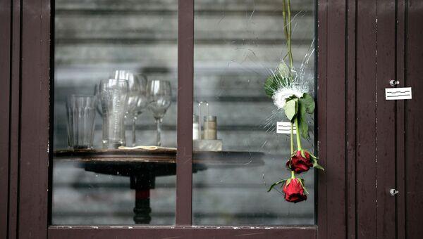 Цветы в пулевом отверстии, оставшемся после терактов, в окне парижского кафе