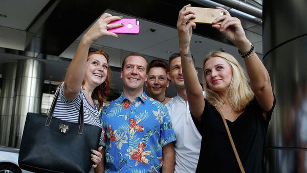 Председатель правительства РФ Дмитрий Медведев фотографируется с российскими и украинскими туристами во время осмотра достопримечательностей столицы Малайзии Куала-Лумпура