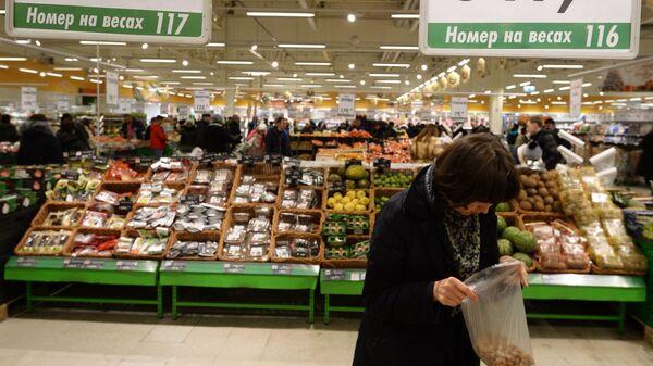 Покупательница у прилавка с орехами в торговом зале гипермаркета Глобус