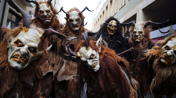 Мужчины одетые как черт Крампус, готовятся к рождественскому параду на рынке Мюнхена