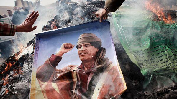 Портрет Муамара Каддафи, плакаты с его цитатами и Зеленая книга Каддафи