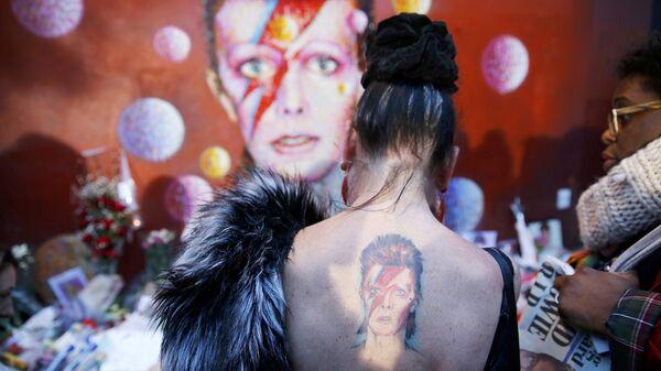 Женщина с татуировкой Ziggy Stardust у стены Дэвида Боуи в Брикстоне. Лондон, январь 2016