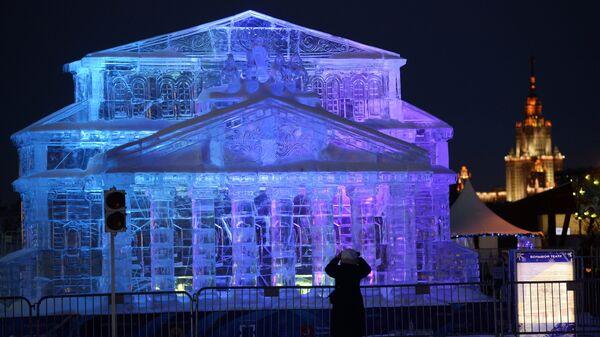 Женщина фотографирует ледяную копию Большого театра на фестивале Ледовая Москва. В кругу семьи в парке Победы