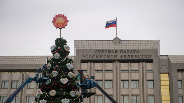 Рабочие украшают новогоднюю елку, установленную у Счётной Палаты РФ