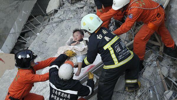 Спасатели помогают ребенку, пострадавшему во время землетрясения на Тайване