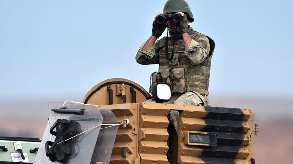 Турецкий солдат наблюдает в бинокль на турецко-сирийский границе