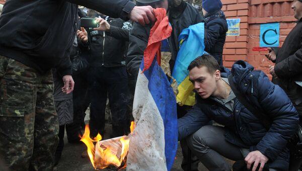Участники митинга с требованием освободить Н. Савченко сжигают российский флаг, сорванный со здания Генерального консульства РФ во Львове. Архивное фото