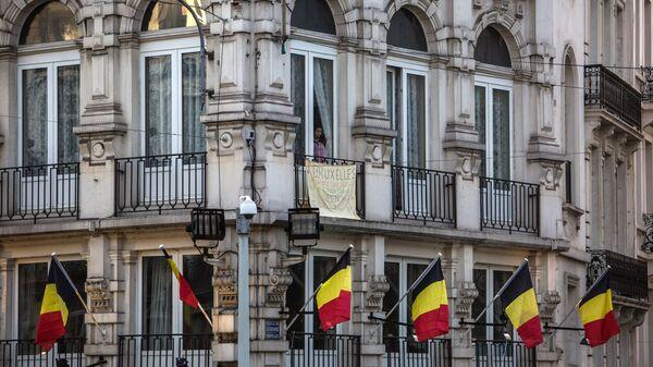 Мужчина в окне здания на Биржевой площади в Брюсселе. Архивное фото