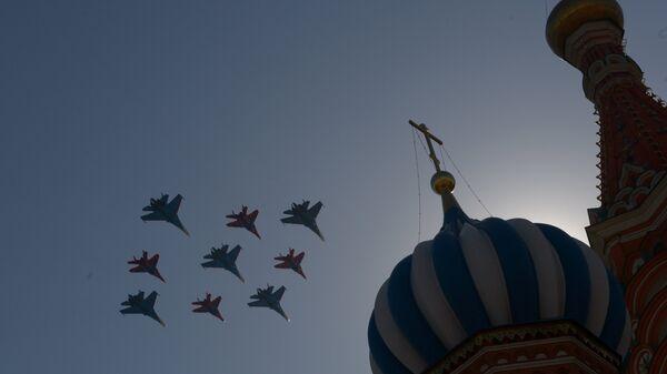 Истребители Су-27 пилотажной группы Русские витязи и МиГ-29 пилотажной группы Стрижи пролетают над Красной площадью