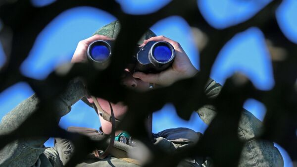 Российский военный смотрит в бинокль. Архивное фото