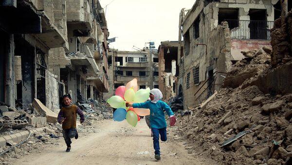 Сирийские дети бегут с воздушными шарами по разрушенной улице в городе Дамаск, апрель 2016