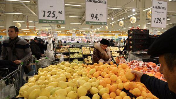 Покупатели у прилавка с лимонами и апельсинами из Турции