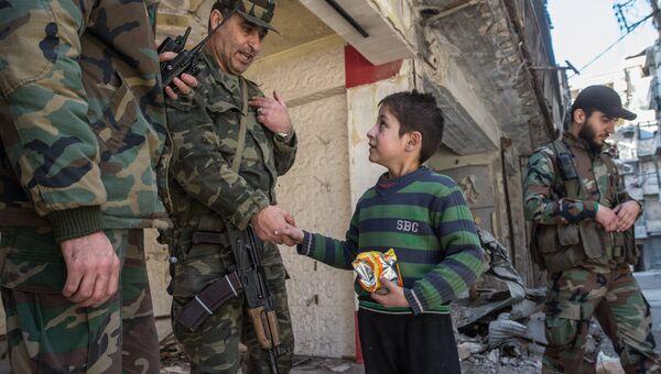 Мальчик общается с военнослужащими Сирийской Арабской армии в жилом квартале города Алеппо. Архивное фото