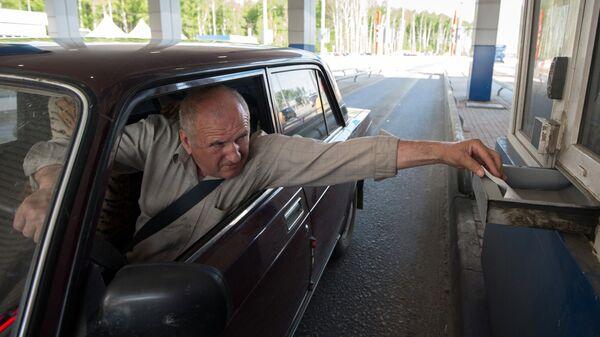 Водитель оплачивает проезд на контрольно-пропускном пункте на платном участке автомобильной дороги М-4 Дон в Московской области