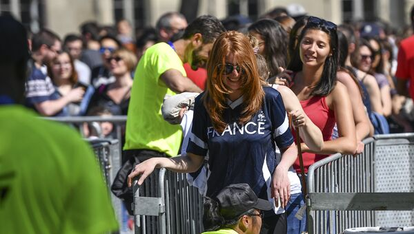 Болельщики заходят в фан-зону Чемпионата Европы по футболу 2016 перед Эйфелевой башней в Париже