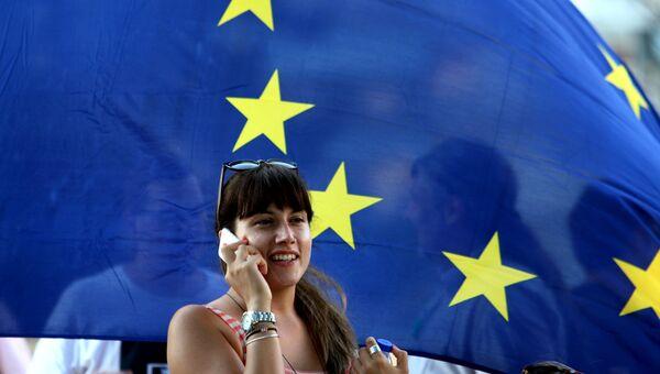 Жительница Афин на фоне флага Евросоюза, Греция. Архивное фото