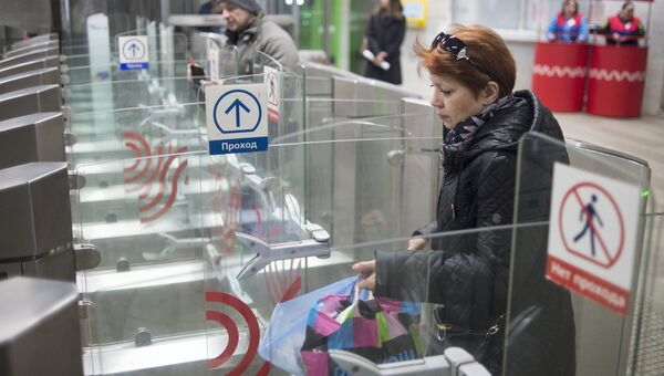 Пассажиры проходят турникеты в вестибюле станции метро. Архивное фото