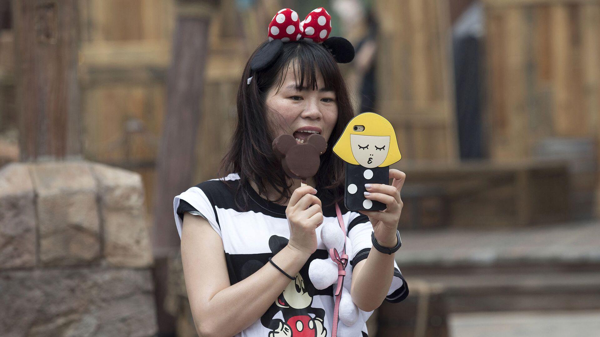 Посетительница первого на территории континентального Китая парка развлечений Диснейленд в Шанхае ест мороженое в виде Микки Мауса - РИА Новости, 1920, 17.01.2021