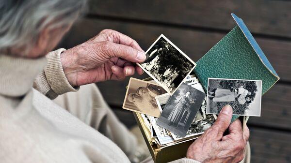 Пожилой человек рассматривает фотографии. Архивное фото
