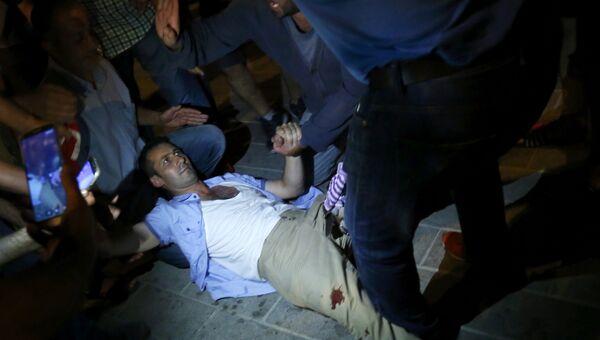 Люди помогают раненому на площади Таксим в Стамбуле