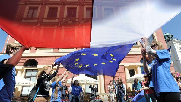 Молодые люди держат флаги Польши и Евросоюза во время демонстрации в Варшаве, Польша