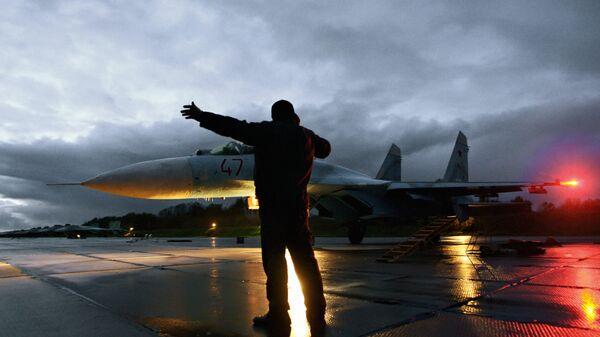 Военный техник дает отмашку на взлет истребителя Су-27. Архивное фото