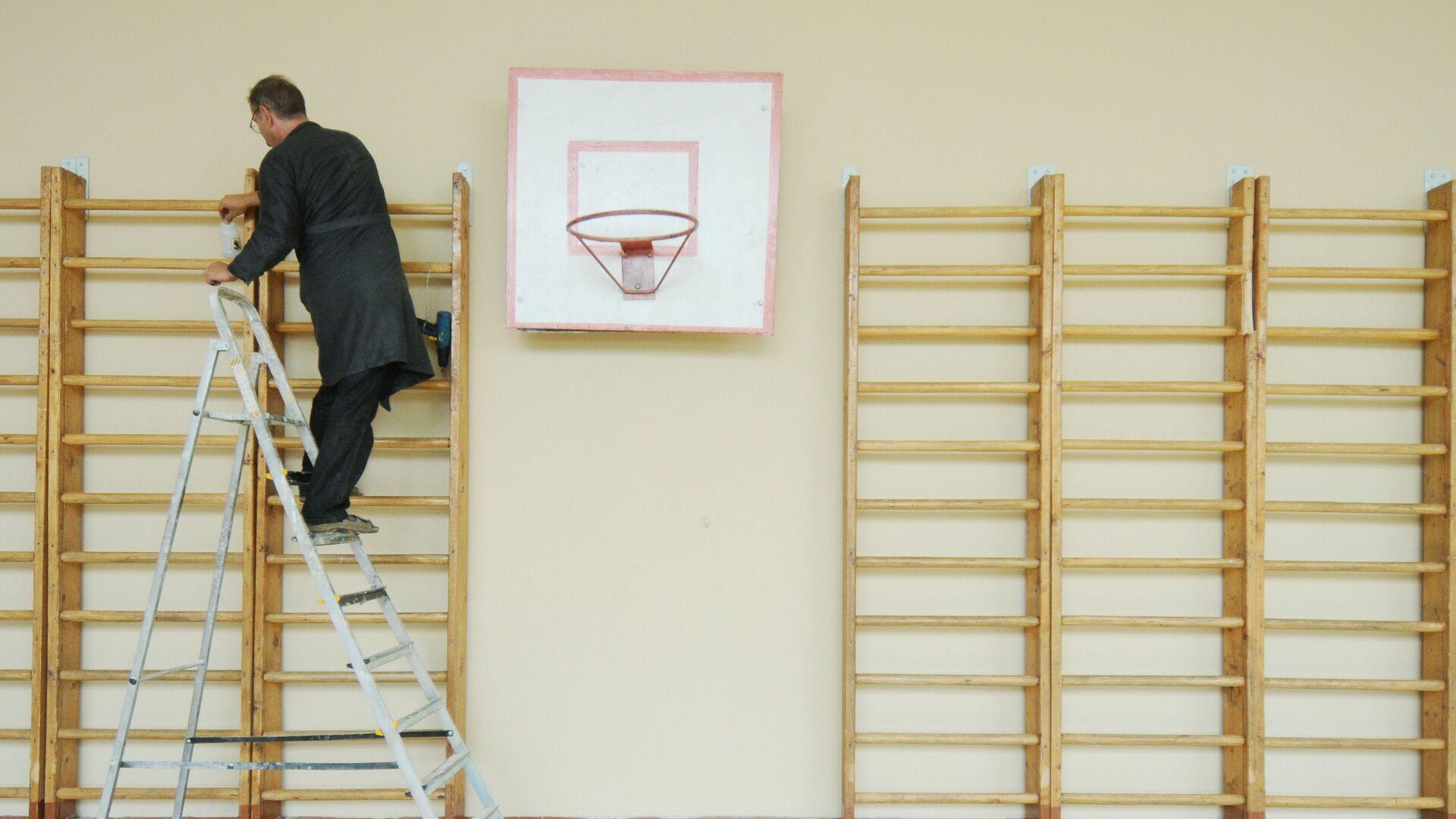 Учитель труда ремонтирует шведскую стенку в спортивном зале школы - РИА Новости, 1920, 04.08.2021