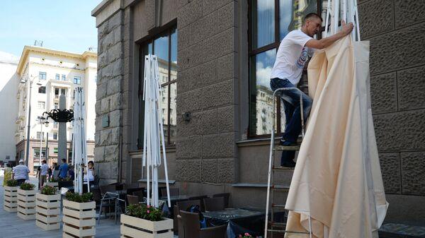 Рабочий устанавливает навес на летней веранде на реконструированной Тверской улице в Москве