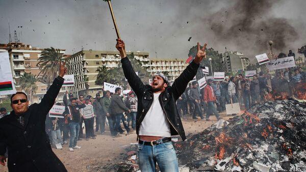 Жители Бенгази сжигают портреты Муамара Каддафи, плакаты с его цитатами и Зеленую книгу Каддафи. Март 2011 года