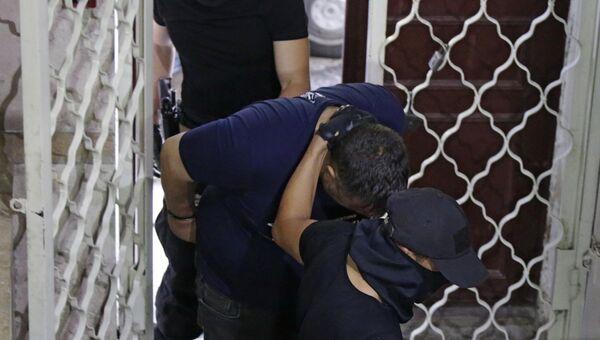 Сотрудники ФСБ вводят в Киевский районный суд Симферополя подозреваемого в организации терактов в Крыму Евгения Панова