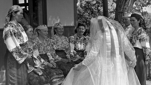 Свадьба на Украине. Невеста демонстрирует подвенечное платье женщинам села перед выходом к жениху