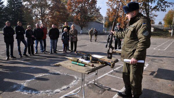Военнослужащий показывает оружие призывникам в День открытых дверей. Львов